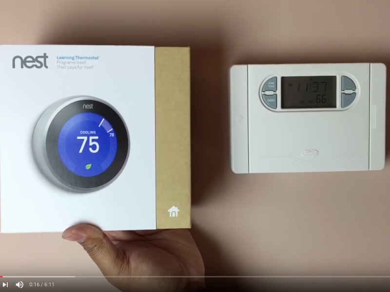 Screen capture from installation video on YouTube: a hand holding up a Nest thermostat, still in its box, near the thermostat to be replaced